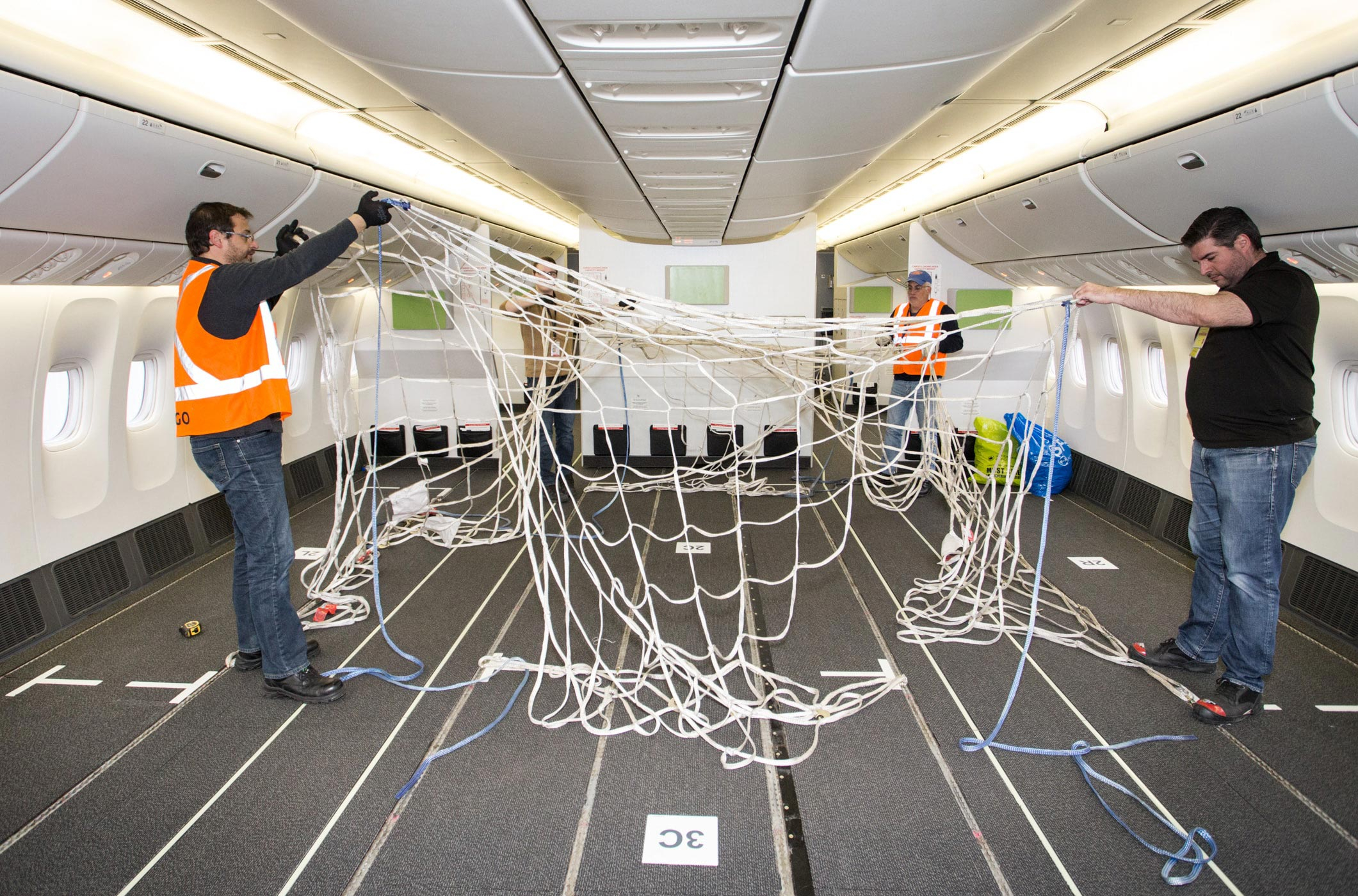 Boeing 777-300ER aircraft being modified to transport cargo in the passenger cabin, doubling cargo capacity.