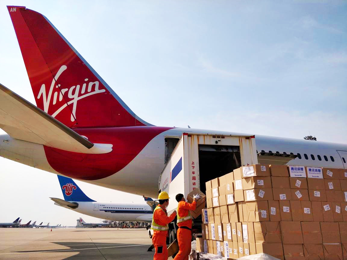 Cargo handlers loading medical shipments onto Boeing 787-9 aircraft